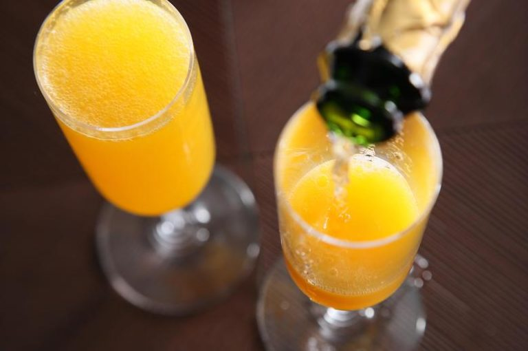 pouring champagne into a mimosa
